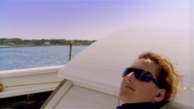 vidéos et rushes de medium shot woman wearing sunglasses reclining aboard ship - intérieur de véhicule