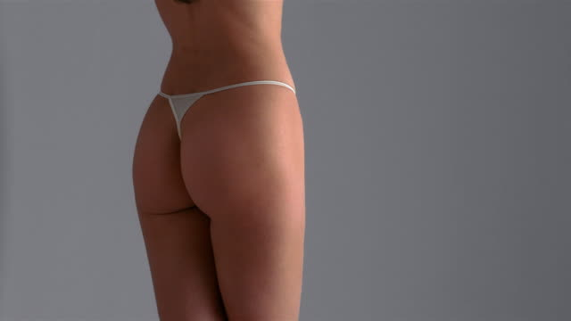 vidéos et rushes de medium shot woman wearing thong underwear standing on spinning turntable / london - underwear