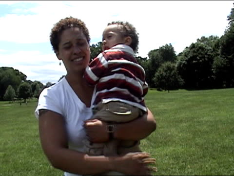 medium shot woman with fussy toddler standing in park and sticking out rolled tongue/ brooklyn - menschliche gliedmaßen stock-videos und b-roll-filmmaterial