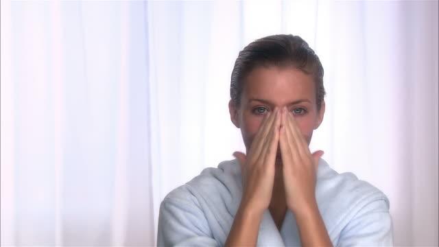 medium shot woman with wet hair wearing bathrobe applying face cream - moisturiser stock videos and b-roll footage