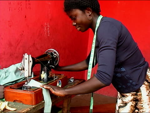 medium shot woman working on sewing machine/ zoom in close up machine/ zoom out woman sewing/ ghana - ghana stock videos & royalty-free footage