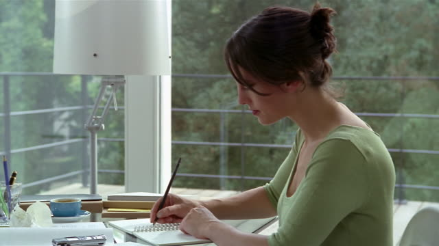 stockvideo's en b-roll-footage met medium shot woman writing in journal at desk by window / balcony and trees in background - dagboek