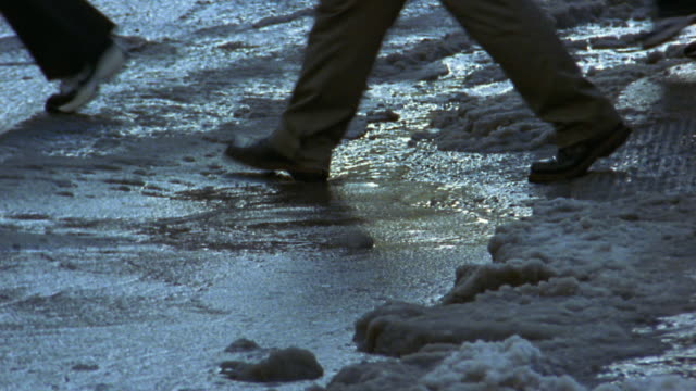 Medium shot woman's boot stepping into slushy puddle / other pedestrians avoiding puddle