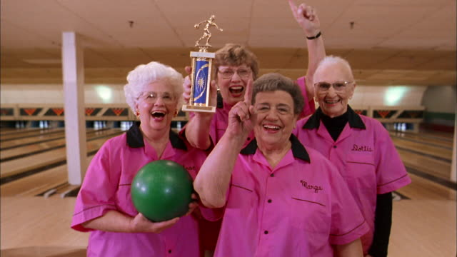 medium shot woman's bowling team in pink jerseys holding trophy / smiling and gesturing at cam - trikot stock-videos und b-roll-filmmaterial