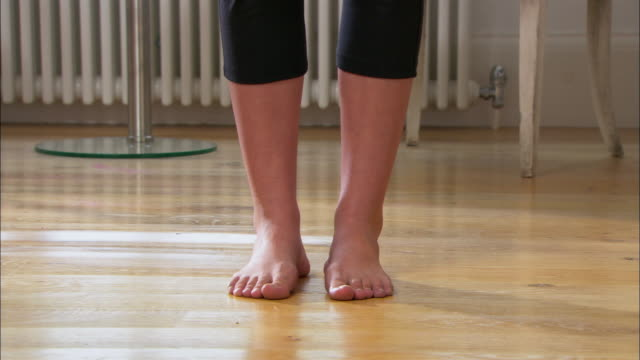 medium shot woman's feet on wood floor/ tilt up young woman doing yoga in living room/ london - nur junge frauen stock-videos und b-roll-filmmaterial