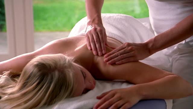 vídeos y material grabado en eventos de stock de medium shot woman's hands massaging shoulder and arm of blonde woman lying on table - de cara al suelo