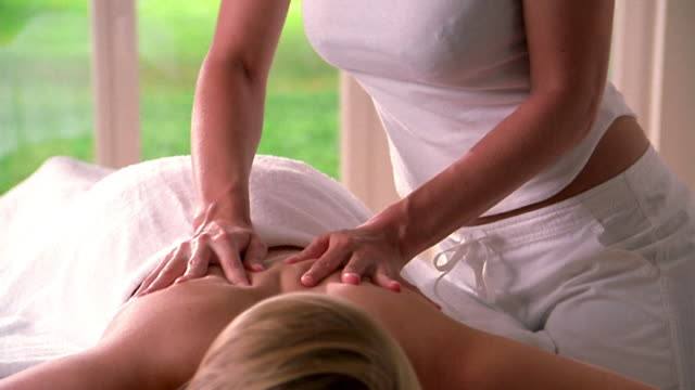 medium shot woman's hands massaging upper back of woman lying on table w/towel covering her lower body - massage table stock-videos und b-roll-filmmaterial