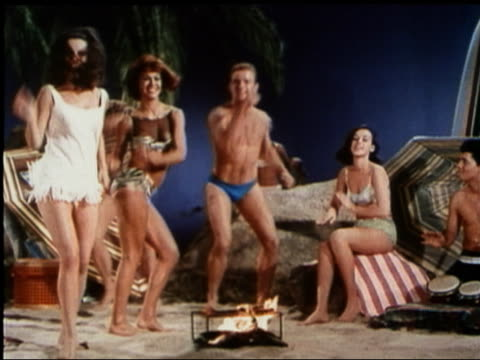 1965 medium shot women and man dancing around fire on beach party film set - bikini stock-videos und b-roll-filmmaterial