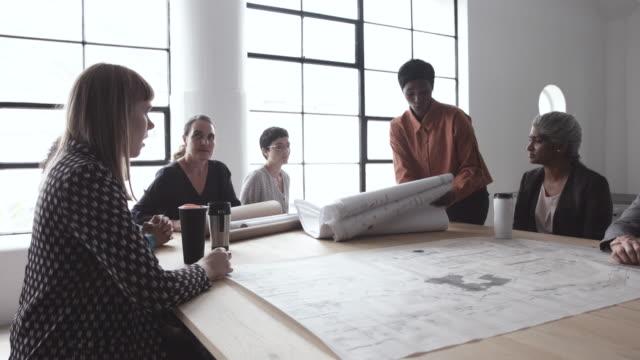 vídeos de stock e filmes b-roll de medium shot, women discuss blueprints at architecture firm - arquiteta