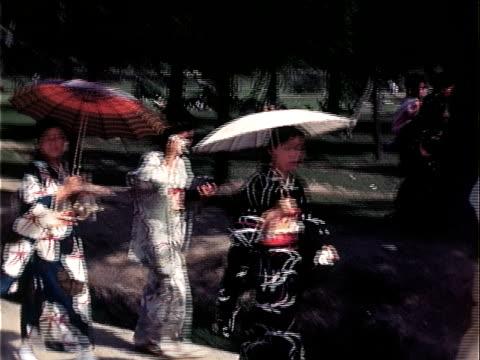 1939 medium shot women in kimonos walking and holding umbrellas/ japan - 1930~1939年点の映像素材/bロール