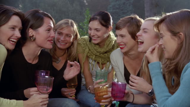 Medium shot women talking and laughing over drinks at party