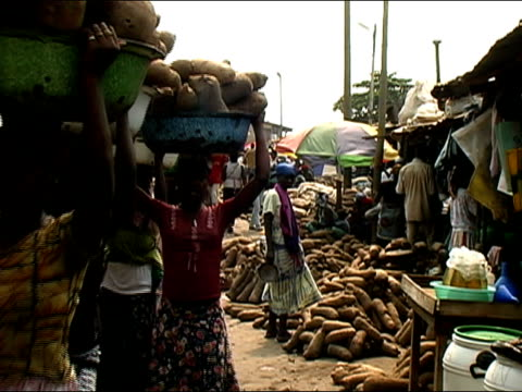 Medium shot women walking though market with tubs of vegetables on their heads/ Ghana