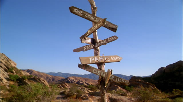 vidéos et rushes de medium shot wooden sign in desert pointing to national and international cities - panneau
