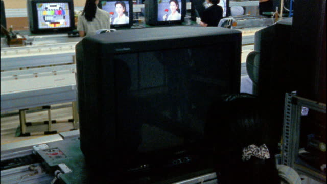 Medium shot worker adjusting picture of television sets on assembly line / Seoul, South Korea