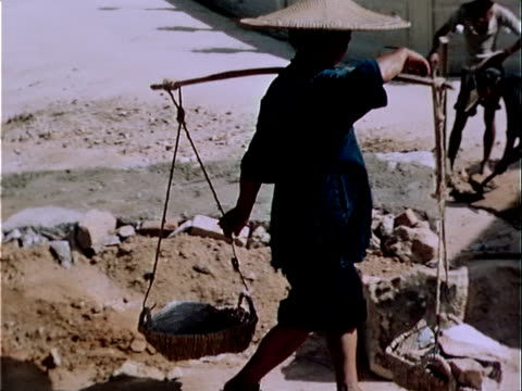1939 Medium shot worker carrying baskets on shoulders at construction site/ Hong Kong