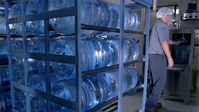 medium shot worker loading water cooler jugs onto rack at water purification plant / san antonio, texas - cooler container stock videos and b-roll footage