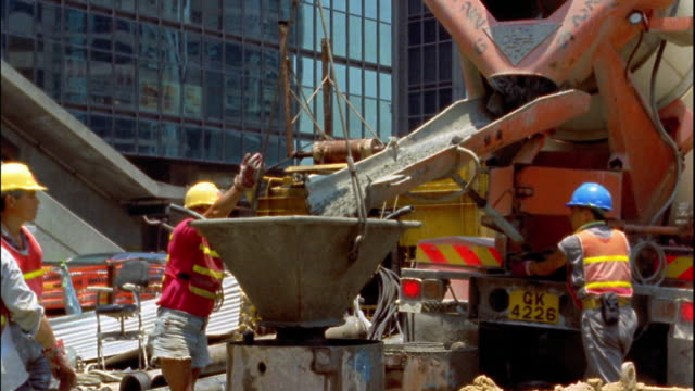 vídeos y material grabado en eventos de stock de medium shot workers monitor cement flowing out of cement truck into large funnel / hong kong - 1996