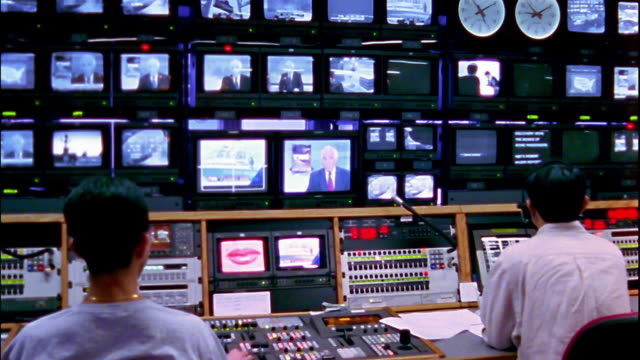 Medium shot workers sitting in television broadcast control room for CNBC Asia bureau / Hong Kong
