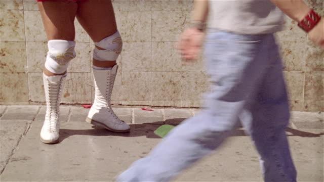 """medium shot wrestler's legs with hat on ground/ tilt up luchador """"black tiger"""" busking with guitar on street/ monterrey, mexico - singen stock-videos und b-roll-filmmaterial"""
