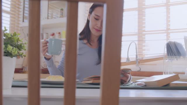 中程度のショットpov 若い大人のアジアの女性は台所で本を読んでいます。自宅でリラックスしながらアナログブックの歴史を勉強している女性。日々の生活活動で学び、知識、教育、リラッ - 本点の映像素材/bロール