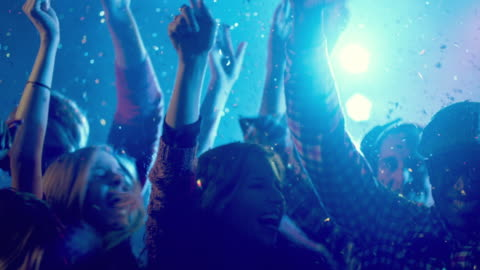 medium shot young adult males and females dancing under glitter, tilt up to hands close up (slo-mo) - konzert stock-videos und b-roll-filmmaterial