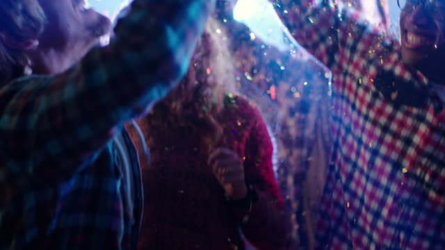 Medium shot young adult males and females dancing under glitter, tilt up to hands close up (slo-mo)