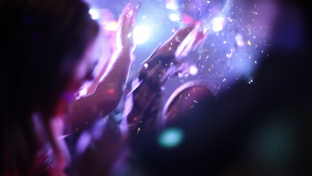Medium shot young adult males and females dancing under glitter