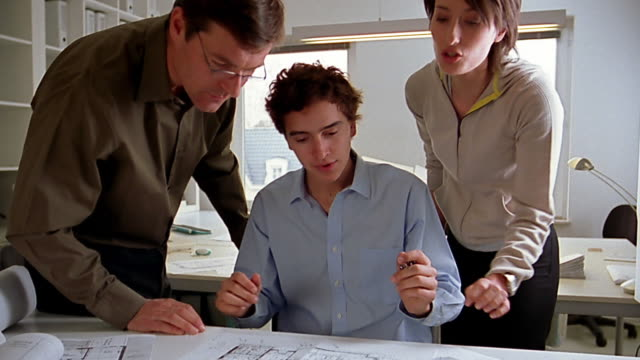 Medium shot young architect discussing blueprints with coworker in office