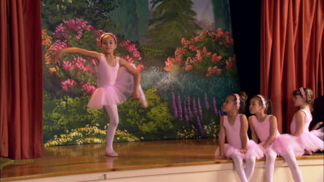 Medium shot young ballerina dancing on stage / other girls and teacher sitting on edge of stage and watching / clapping as ballerina curtsies