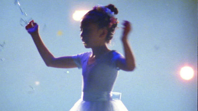 Medium shot young ballerina in blue tutu spinning w/confetti falling against bright lights in background