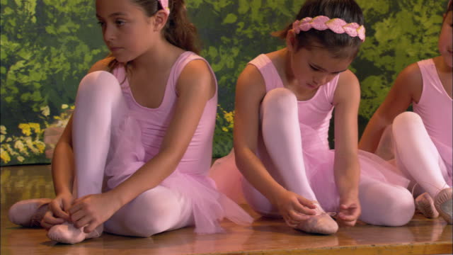 medium shot young ballerinas sitting on stage tying shoes - ballet shoe stock videos and b-roll footage