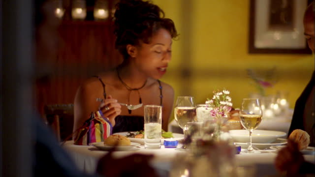 vidéos et rushes de medium shot young black couple eating dinner and talking w/glasses of wine , food + water on table - romantisme