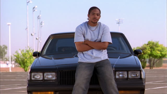 vidéos et rushes de medium shot young black man leaning against car hood and looking at cam - s'appuyant