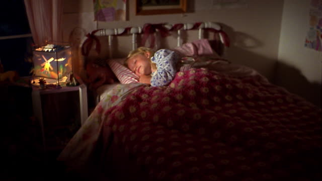 Medium shot young blonde girl sleeping in bed next to bedside table w/lamp
