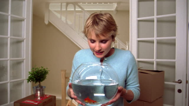 medium shot young blonde woman holding goldfish bowl / raising bowl up to her face playfully and talking - goldfish stock videos & royalty-free footage