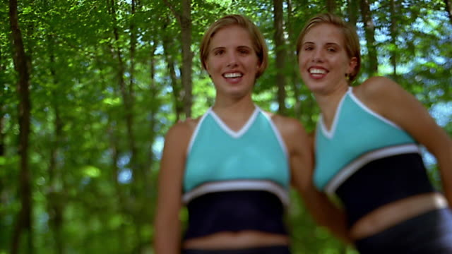 Medium shot young blonde woman / triplet sisters joining her / hugging and posing / forest in background