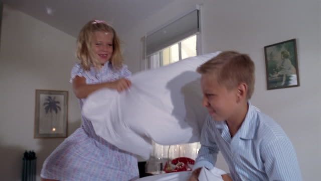 medium shot young boy and girl having pillow fight on bed / feathers flying / miami, florida - 枕投げ点の映像素材/bロール