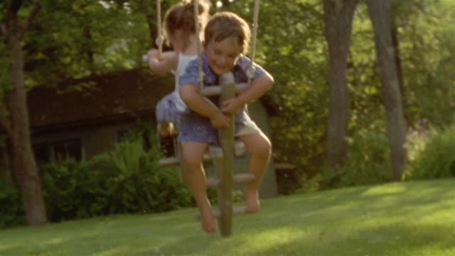 medium shot young boy and girl on swing on sunny afternoon - schwingen stock-videos und b-roll-filmmaterial