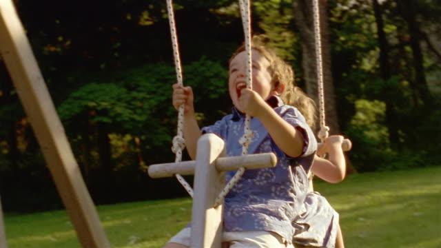 medium shot young boy and girl on swing - 屋外遊具点の映像素材/bロール