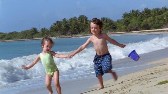 Medium shot young boy and girl running on beach