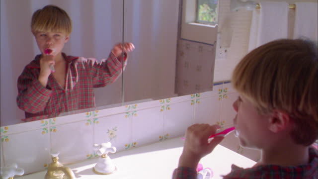 medium shot young boy brushing his teeth in bathroom mirror - brushing teeth stock videos & royalty-free footage