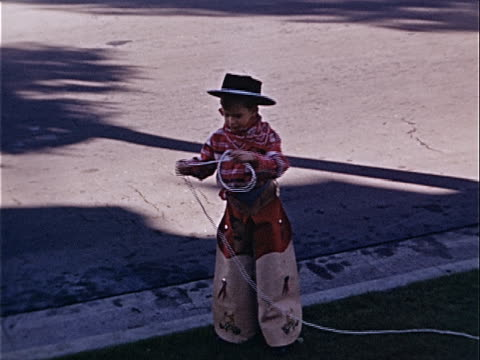 stockvideo's en b-roll-footage met 1940 medium shot young boy curling lasso and wearing cowboy costume in street / los angeles, california, usa  - cowboyhoed