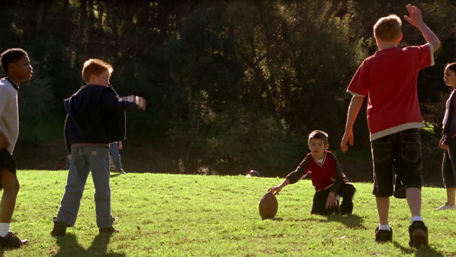 vidéos et rushes de medium shot young boy holding football / another boy kicking off / kids running towards ball - 10 11 ans