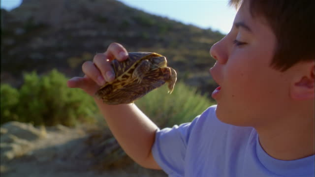 Medium shot young boy holding turtle on desert hiking trail