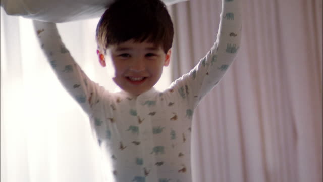 medium shot young boy in pajamas smiling and throwing pillow toward cam - pillow fight stock videos & royalty-free footage