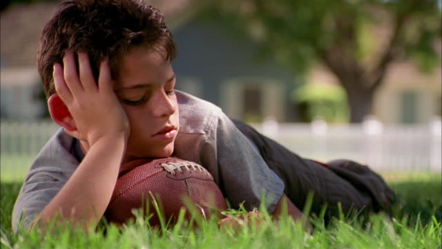 medium shot young boy laying outdoors w/chin on football and picking grass blades - negative emotion stock videos & royalty-free footage
