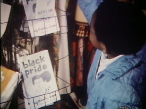 vídeos de stock, filmes e b-roll de 1969 medium shot young boy looking at black pride book in bookstore - livraria