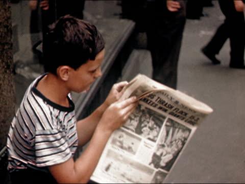 1945 Medium shot young boy reading newspaper on New York City street/ AUDIO