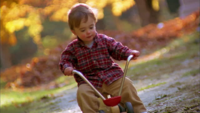 medium shot young boy sitting on tricycle and walking along w/autumn foliage in background - tricycle stock videos and b-roll footage