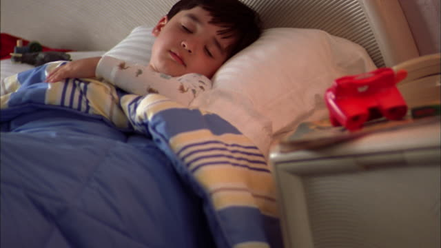 medium shot young boy sleeping under blankets in bed - schlafenszeit stock-videos und b-roll-filmmaterial